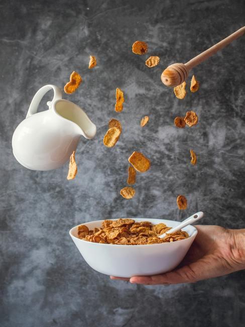 Bol con copos de maiz cayendo, una jarra de leche y miel