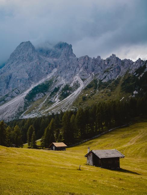 Macizo montañoso y rocoso con prado, árboles y dos refugios en primer plano