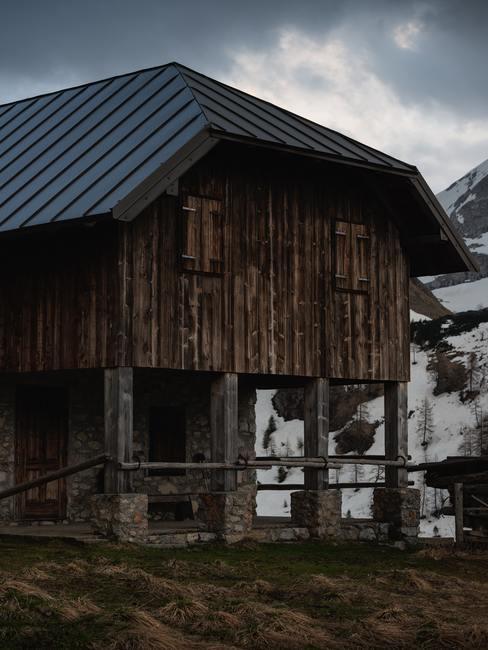 Chalet de piedra y madera en montaña con campo nevado al fondo