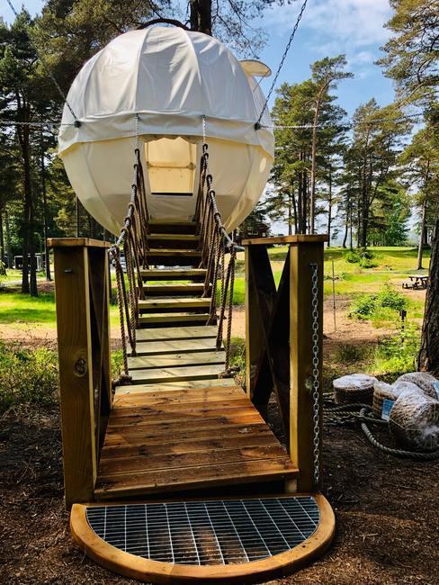Tienda de campaña circular en altura con escaleras de madera para llegar a ella
