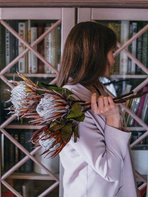 Mujer sujetando tres flores protea delante de una estantería con libros