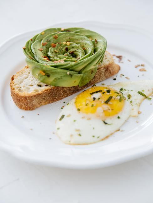 Tostada con aguacate y semillas junto a un huevo frito