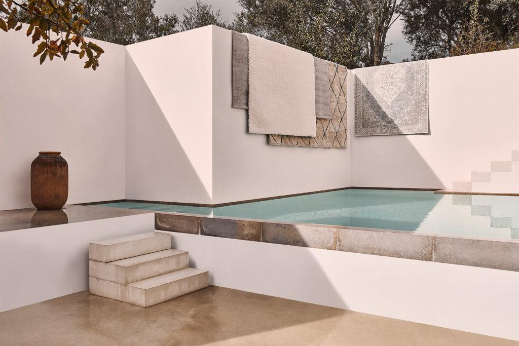 Terraza zen con pequeño estanque o piscina en altura y alfombras colgando