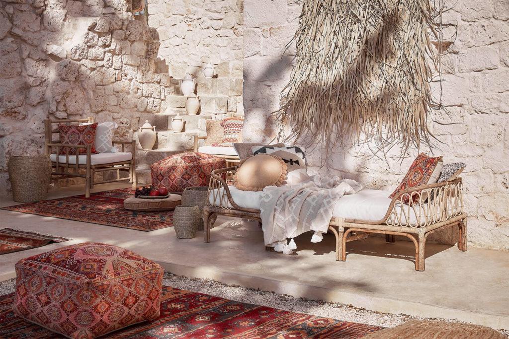 Terraza étnica con decoración oriental, pufs y sillas de madera, con gran muro de piedra