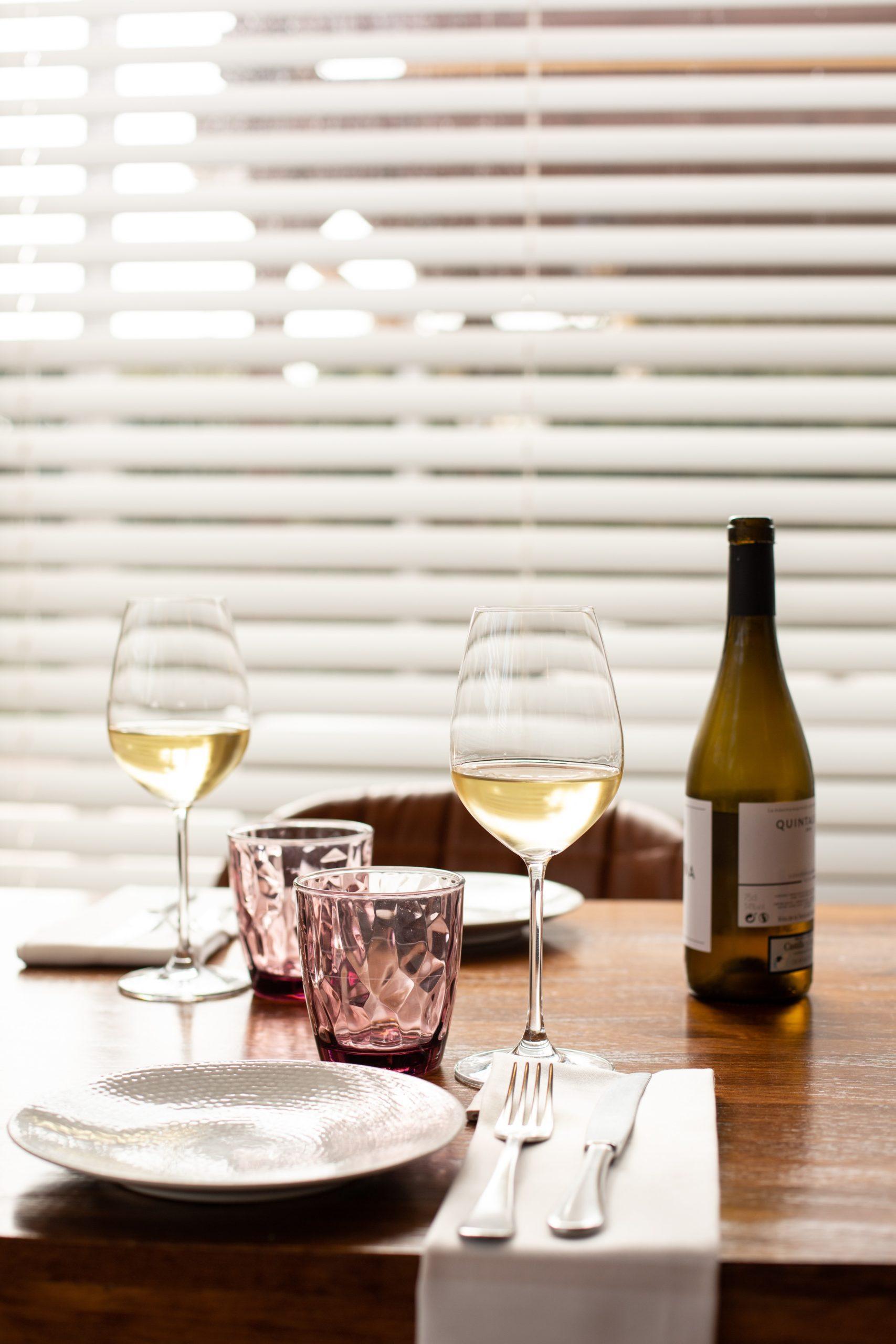 Mesa para cena romántica con dos copas de vino blanco y una botella