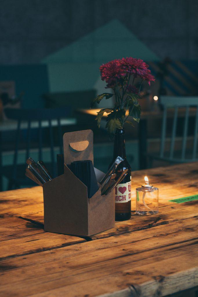 Mesa de madera con cubiertos y flores metidas dentro de una botella de vino, junto a un portavelas de cristal con una vela encendida