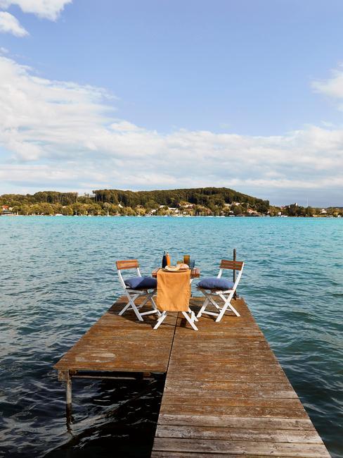 Pequeño muelle sobre un lago con mesa y sillas al final