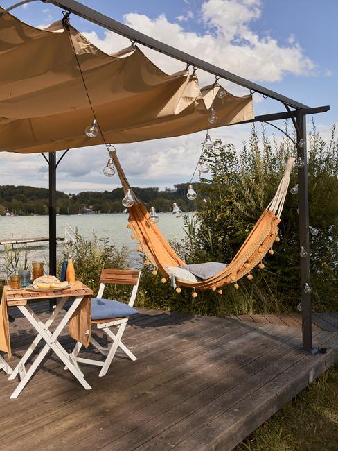 Vacaciones glamping con tarima al borde de un lago, hamaca, mesa y sillas de madera