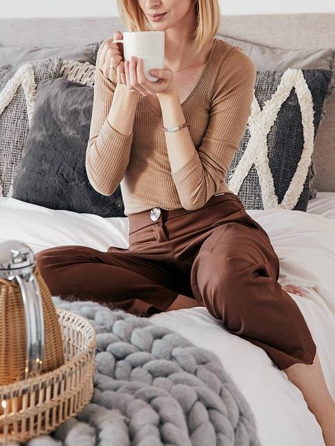 mujer toma una taza de café en la cama