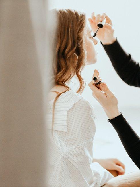 maquilladora aplica rimmel a mujer