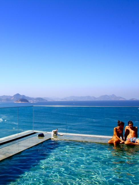 pareja en piscina con mar detras