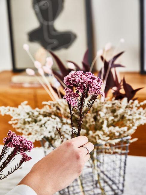 mano coloca una flor artificial en ramo
