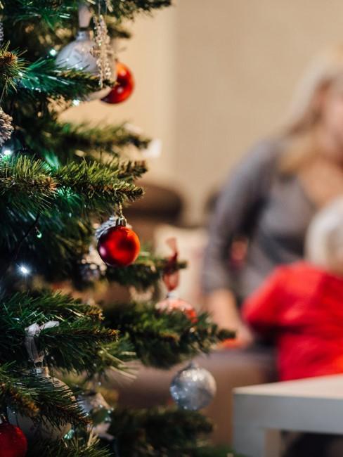 Árbol de navidad con familia detras