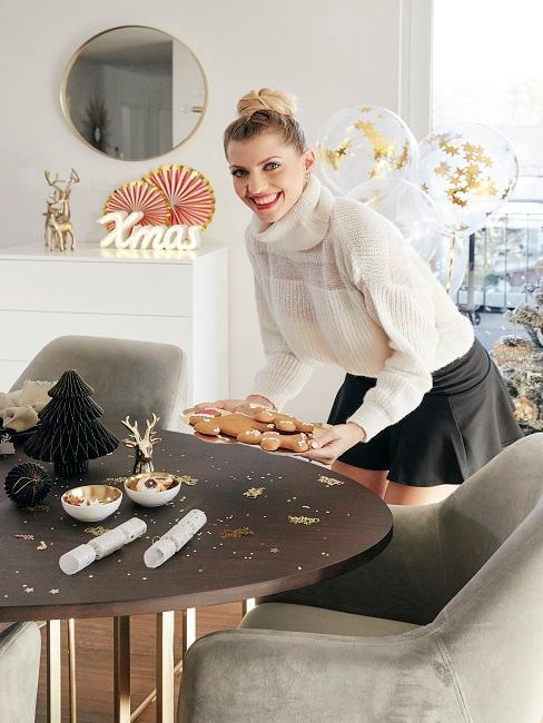 mujer coloca galletas en mesa navideña