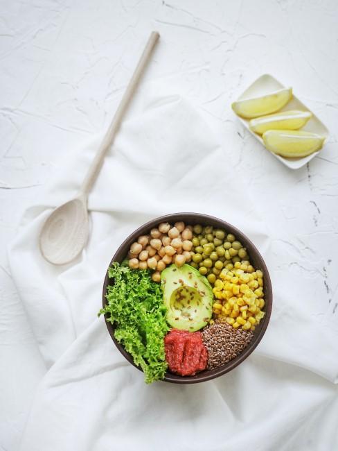 Un bol con garbanzos, aguacartes, tomate, maiz y mas
