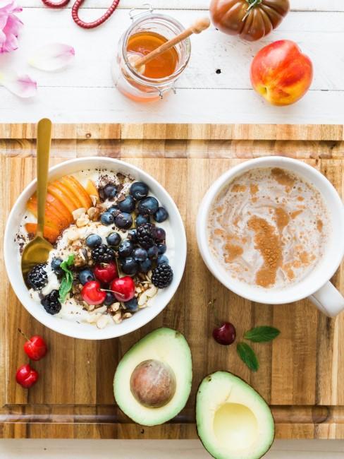 aguacate, cafe, miel y un bowl de frutas