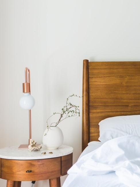 cama de madera con lámpara en cobre