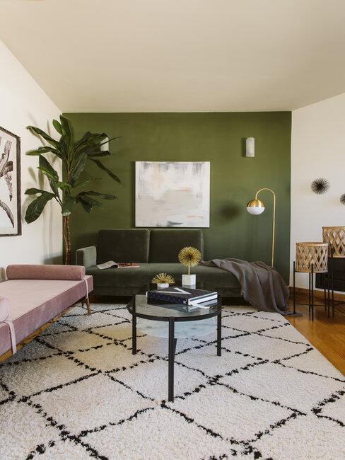 salon con pared verde y blanca alfombra y sofa rosa