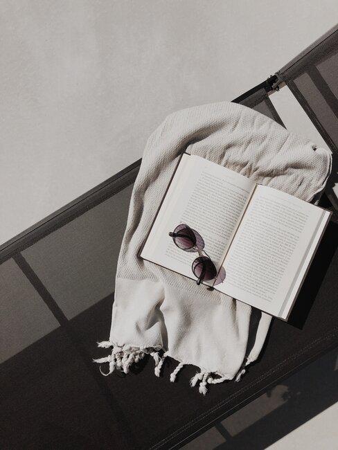 Tumbona con fouta, libro y gafas de sol encima