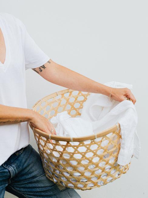 mujer lleva cesto con ropa blanca