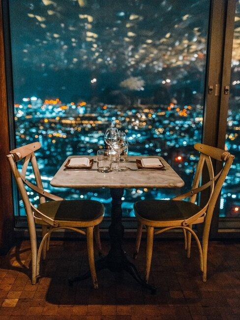 Mesa para dos delante de un gran ventanal en las alturas
