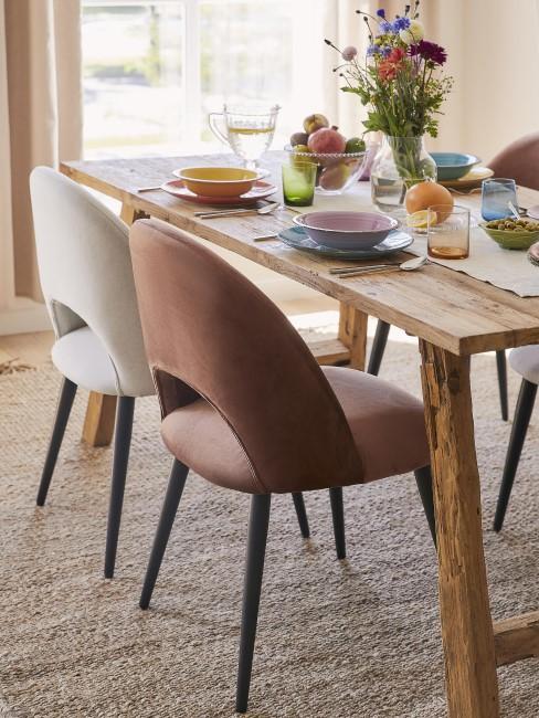 Una silla marrón y otra blanca en una mesa de comedor con cortinas beige