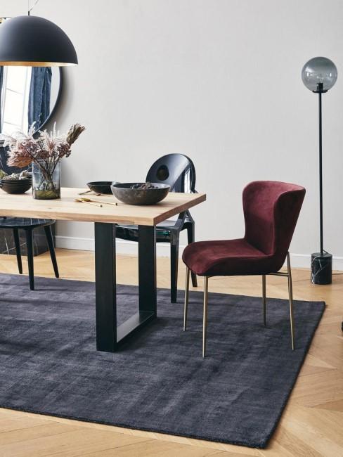 Mesa de comedor con sillas de terciopelo y alfombra gris oscuro