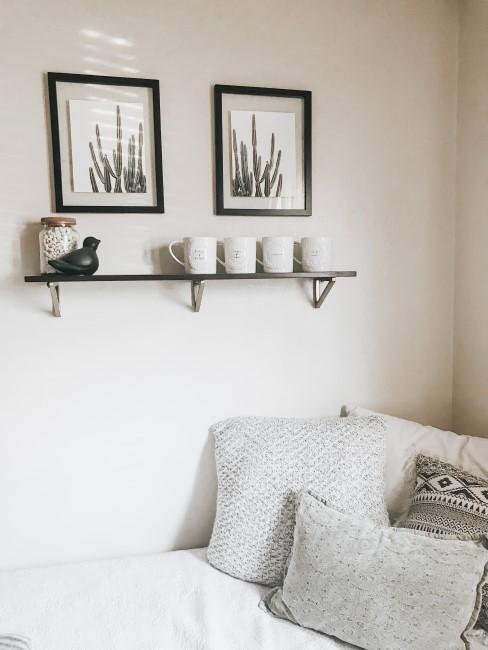 dromitorio blanco con 2 cuadros y un estante