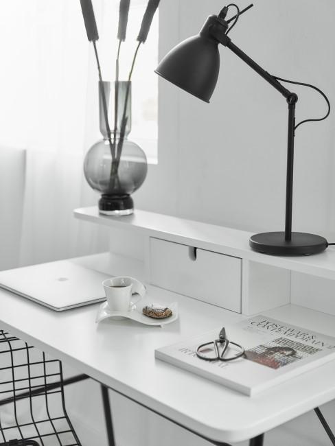 Escritorio blanco con lámpara negra en una oficina en casa