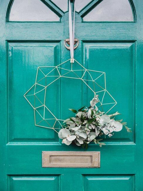 puerta azul con corona moderna y flores
