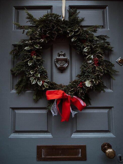 corona de navidad con hojas en la puerta