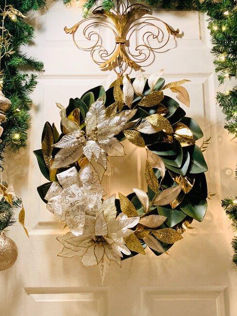 puerta blanca con corona navideña verde y dorada