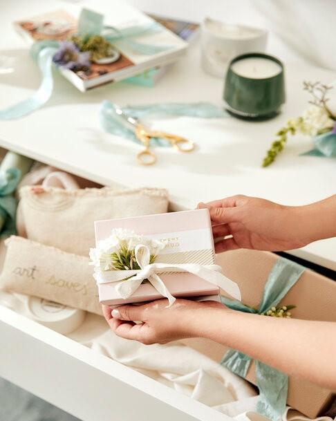 manos sostienen regalo rosa con flores