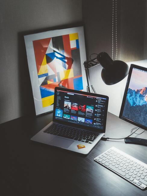 escritorio con ordenadores y cuadro abstracto en una esquina