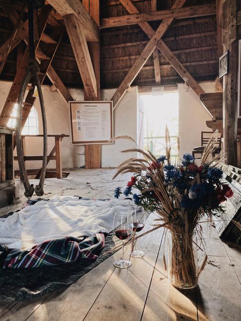 habitación original con suelo y techo de madera, grandes vigas de madera y flores