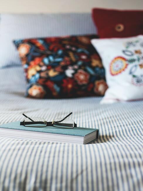 cama con cojines, libro y gafas