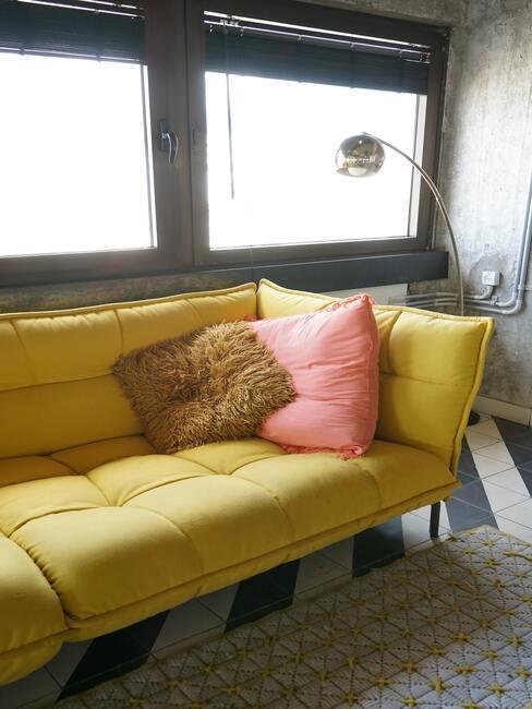 sofá amarillo con cojines marrón y rosa y lámpara de pie de estilo industrial