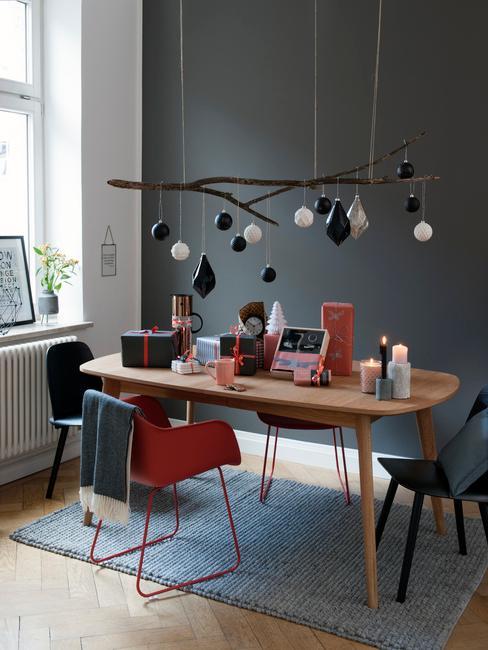 Mesa de madera preparada para invitados con regalos y lámpara de diseño colgante por encima