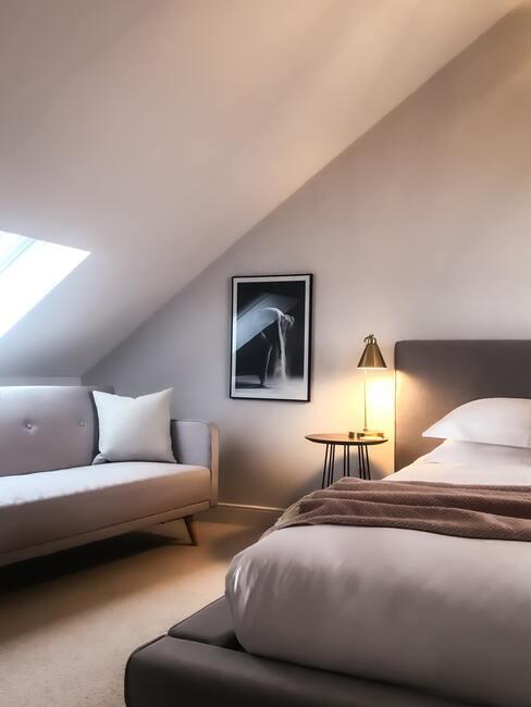 Dormitorio abuhardillado con cama y sofá en tonos grises