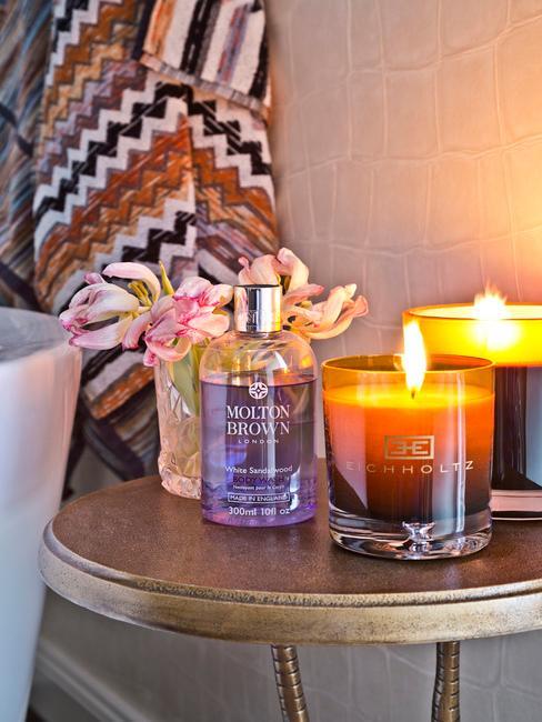 mesa de noche de metal sobre la que descansan difusores de perfume, flores y velas