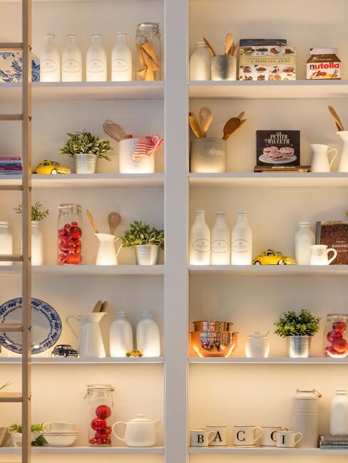 Grandes estanterías de madera blanca con utensilios de cocina, jarrones y tazas