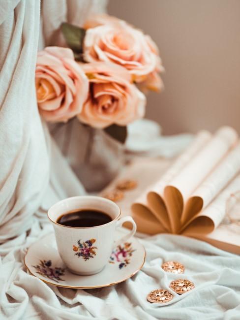 cafe en una taza de porceana, con un libro y rosa color salmon