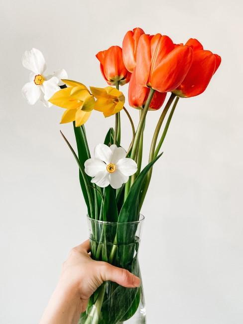 jarrón con flores y una mano sujetandolo
