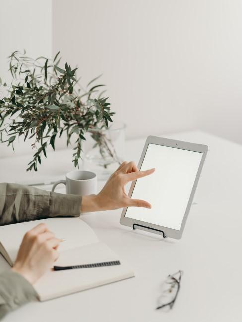 Persona trabanjando con un ipad y un book de notas