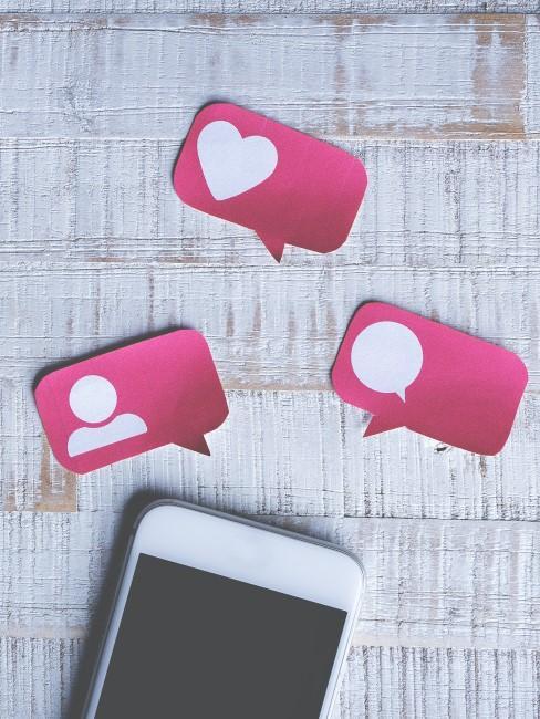 Movil con emojis de comentarios, likes y personas