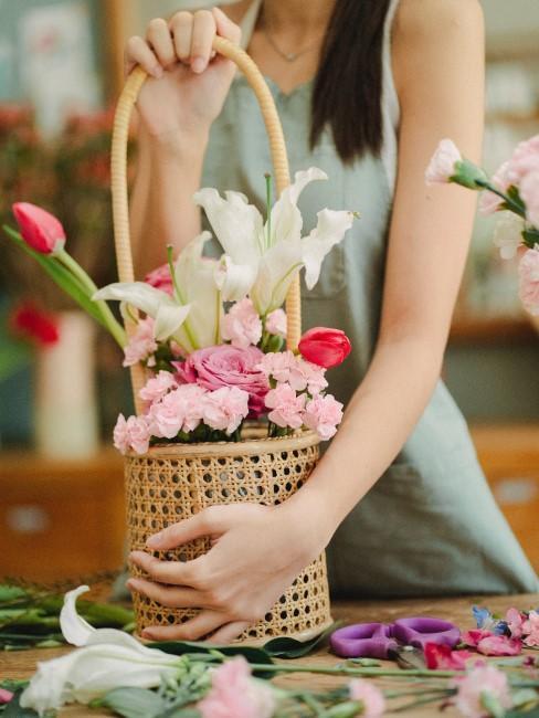 mujer preparando un cestas con flores rosas y blancas