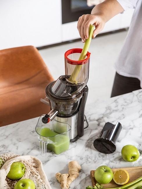 mujer prepara zumo de manzana con máquina