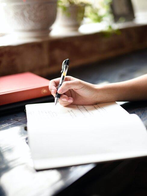 mujer escribe en un cuaderno blanco