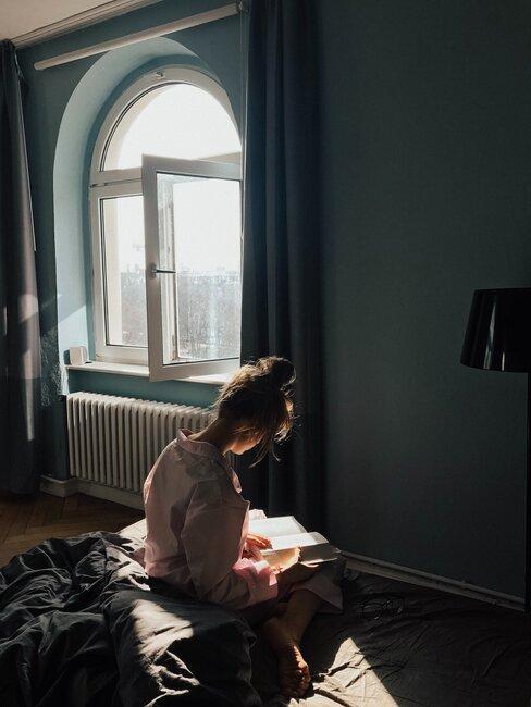 mujer lee libro en el dormitorio con la venta abierta