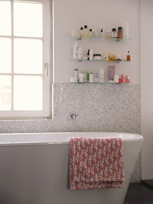 bañera y estantes con productos de lujo en baño